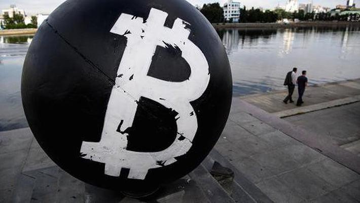 Biểu tượng Bitcoin trên một quả cầu bằng đá sơn đen đặt trên một quảng trường ở thành phố Yekaterinburg Nga